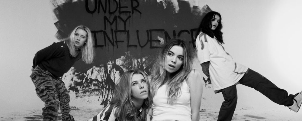 The girl band pose in front of graffiti wall that says 'Under my influence'.