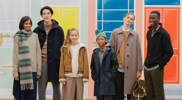 Adults and children pose in front of pastel background. They are wearing fall and winter outfits.