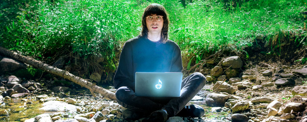 A. G. Cook sits in bright green forrest with his laptop.